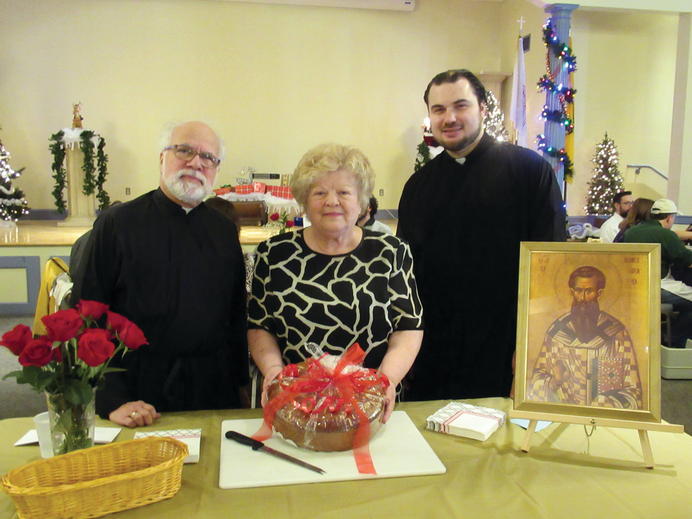 CHAIR'S CORNER: Kate Silva, center, who chaired Sunday's unique Philoptochos Vasilopeta Luncheon, is joined by Church of the Annunciation Pastor Rev. Andrew George, left, and Father Nick Lanzourakis prior to the cutting of the Saint Basil's Bread.