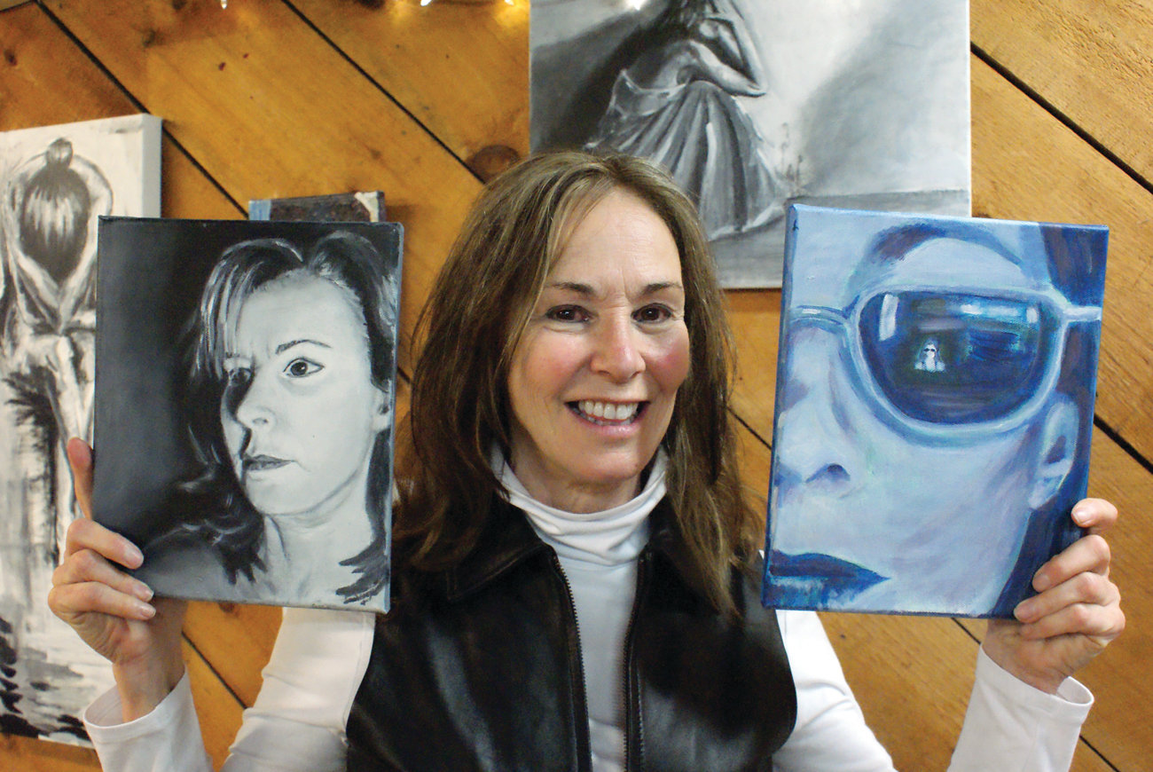 SELF PORTRAITS: Among her artwork on display this past Saturday at Dragonfly Studio in Cranston, Jean Colaneri posed with two of her self-portraits.