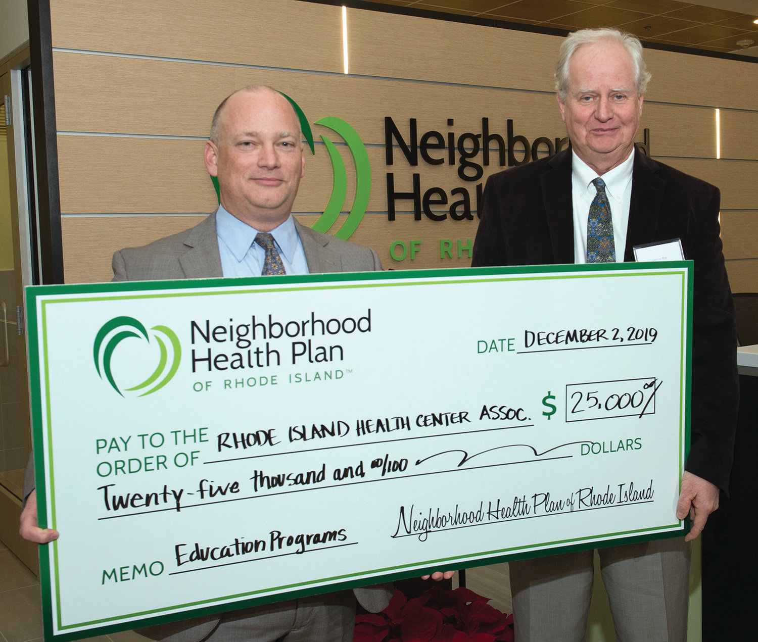 GENEROSITY ON DISPLAY: President and CEO Peter Marino (on left) presents a $25,000 check to Rhode Island Health Center Association (RIHCA) as the final donation of Neighborhood's 25th Anniversary Charitable Giving Program. Accepting the check on behalf of RIHCA is Dennis Roy, Neighborhood board member and president and CEO at East Bay Community Action Program. The donation will be used to fund education programming for the state's community health centers.