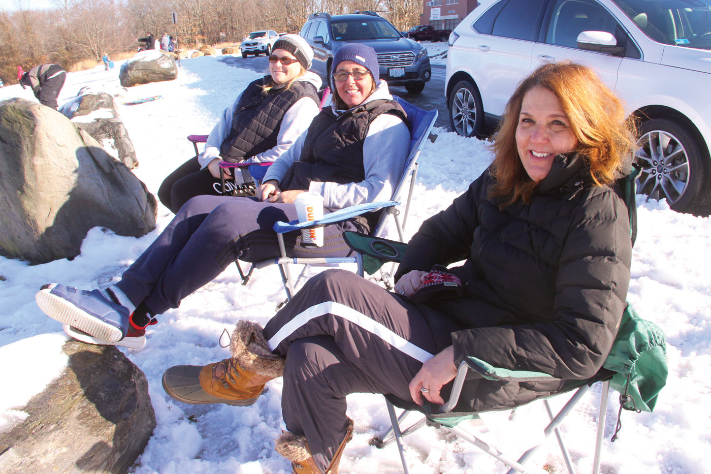 BEACHING IT? Jennifer Ross, Jennifer Izzo and Lori McNulty were prepared to stand or perch on the rocks at the crest of the hill at the school administration building (Gorton Junior High) as the kids they brought along took advantage of the first sledding of the new year. Then Ross remembered the beach chairs she'd never removed from the back of the car. They turned out to be perfect with one of the boulders the ideal footrest for Izzo.