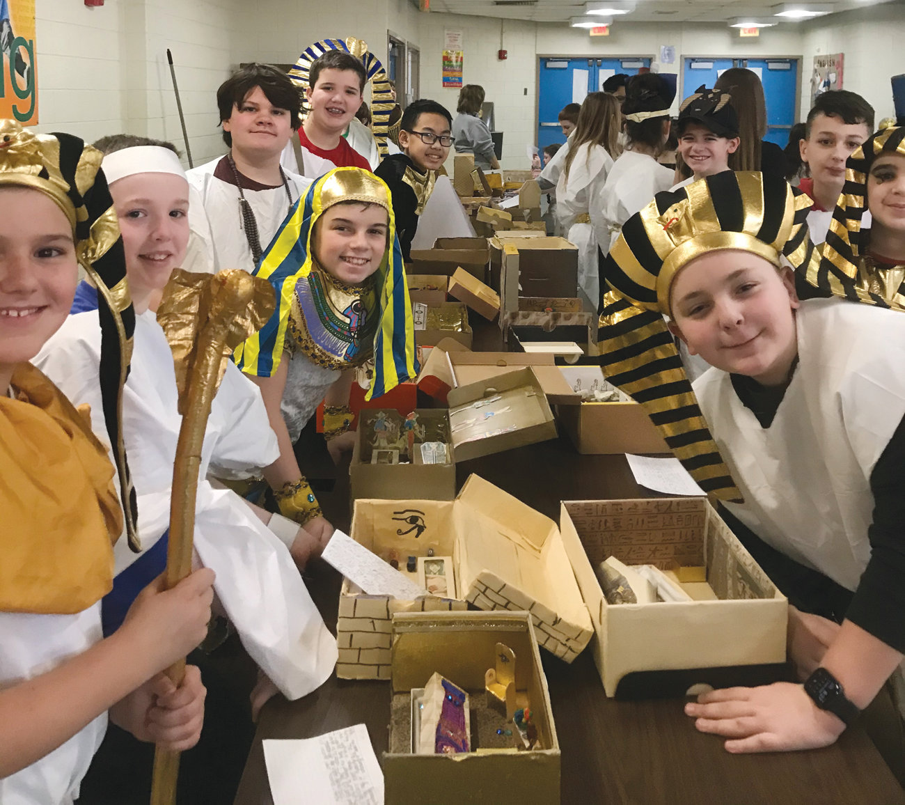 SARCOPHAGUS IN MINIATURE: Winman 6th graders gave a short presentation about their Egyptian identity, daily life, mummification process and burial chamber and an amazing costume taking on the role of their Egyptian person they spent time researching for over 300 parents, family members and guests in attendance on Friday, January 17 in the school cafeteria. Pictured from left (front to back) are Elijah Coons, Jackson Kavanagh, Tiernan Leahy, Benjamin Ashworth, Jacob Arthurs and Michael Xiong; (right row front to back) Benjamin Berry, Andrew Bacon, Tyler McCoombs and Liam Ebbitt.