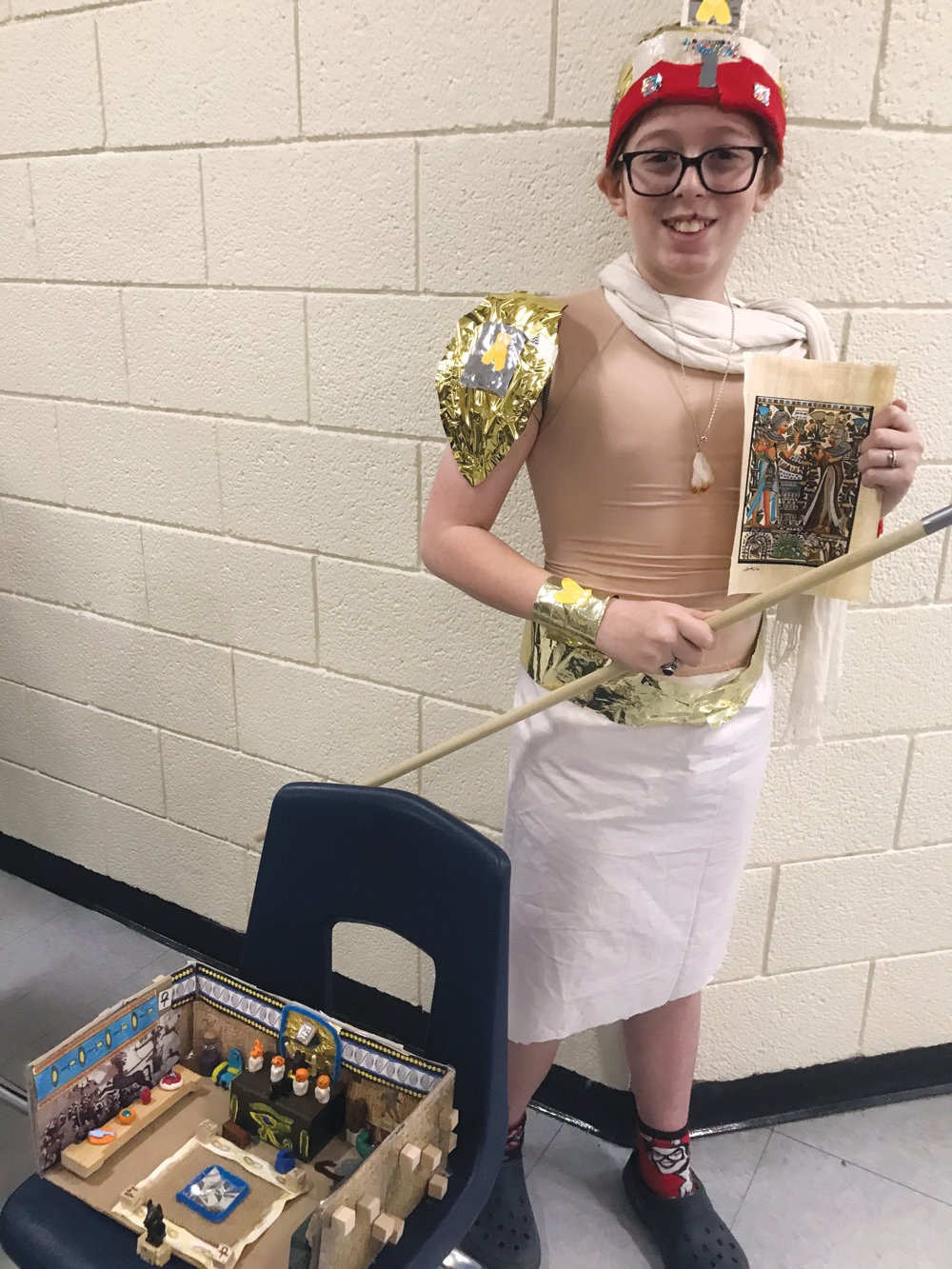 Landon Friedman is holding an Egyptian papyrus from the British Museum (that his dad had gotten for him from a previous trip to London) and his spear as he took on the identity of an ancient Egyptian general and is dressed in costume. He also created a shoebox sarcophagus tomb for his burial chamber.