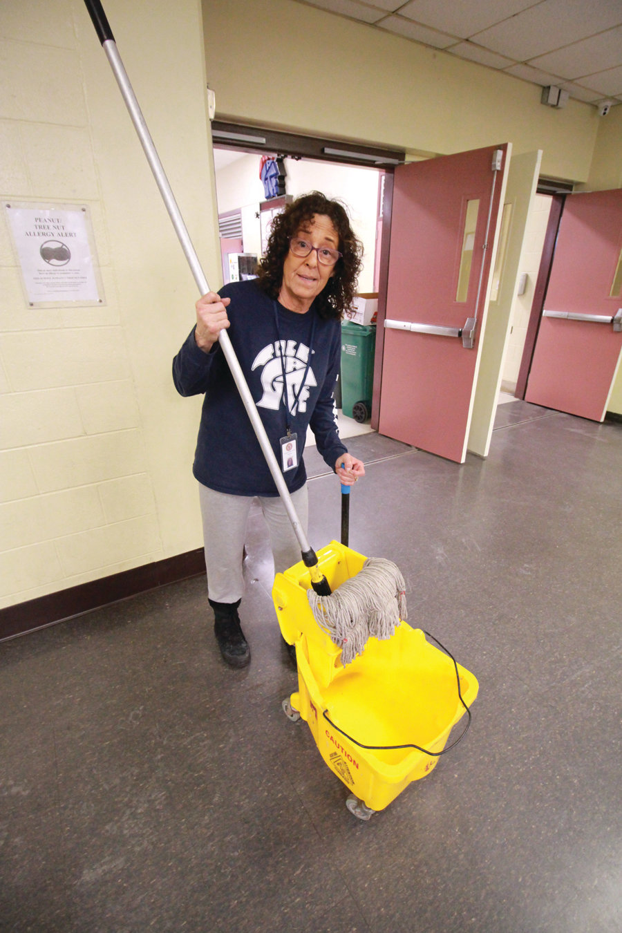 CLEANUP: Custodian Mary Manson mops up the flooding in a hallway on Saturday afternoon.