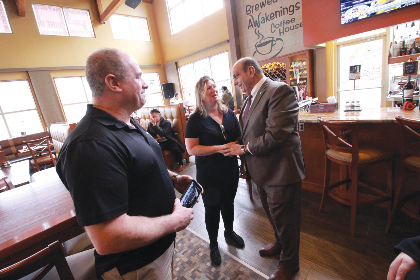 PURSUING HIS VISION: David Levesque, who founded the Rhode Island chair of Brewed Awakenings coffee shops, talks with Warwick Mayor Joseph Solomon on a recent visit to the Bald Hill Road store. David's sister, Karen Dore, who also works at Brewed Awakenings, joins them.