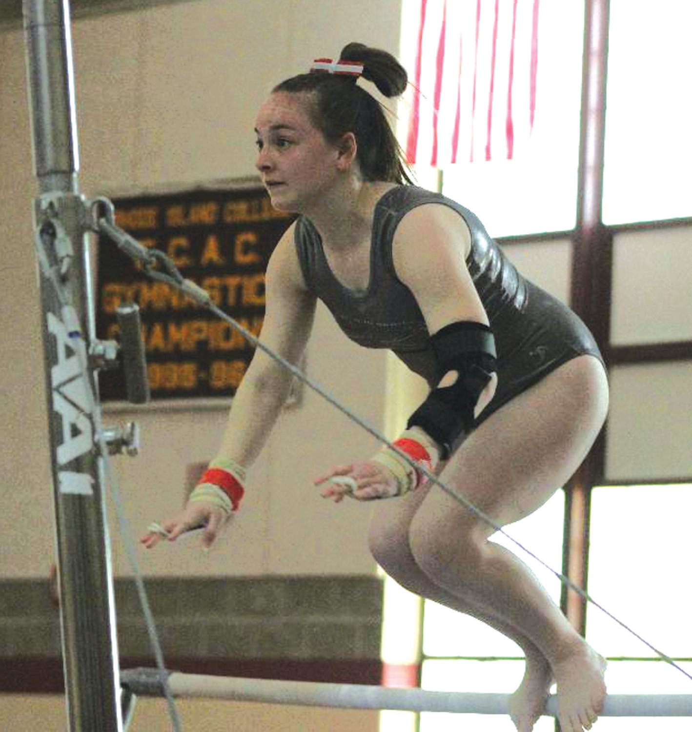 RAISING THE BAR: Cranston West's Emily Parillo competes on the bars at the RIIL Gymnastics State Championships at Rhode Island College last Saturday.