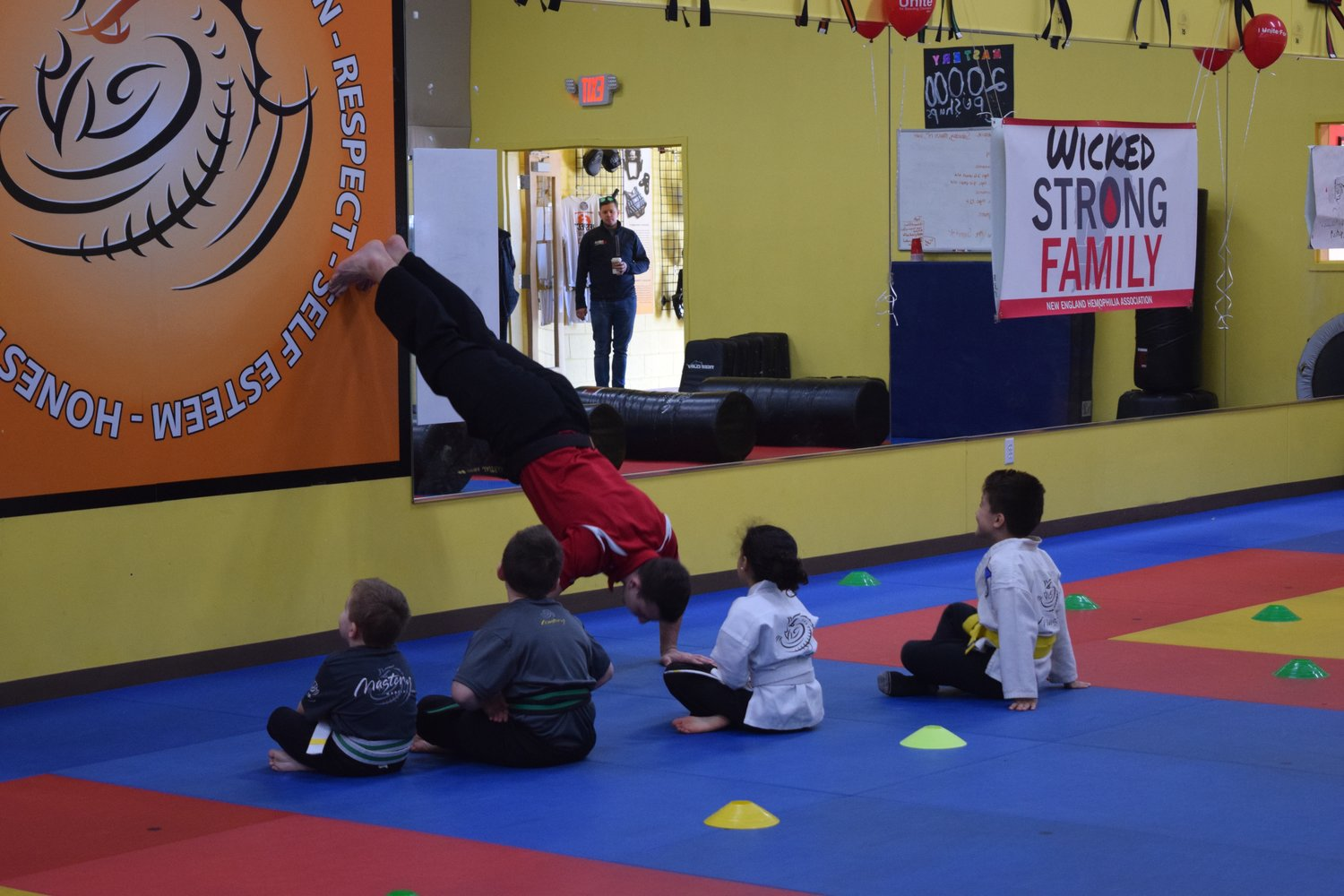 FOR EXAMPLE: Younger Mastery students look on as an older member does an example of a particularly difficult pushup.