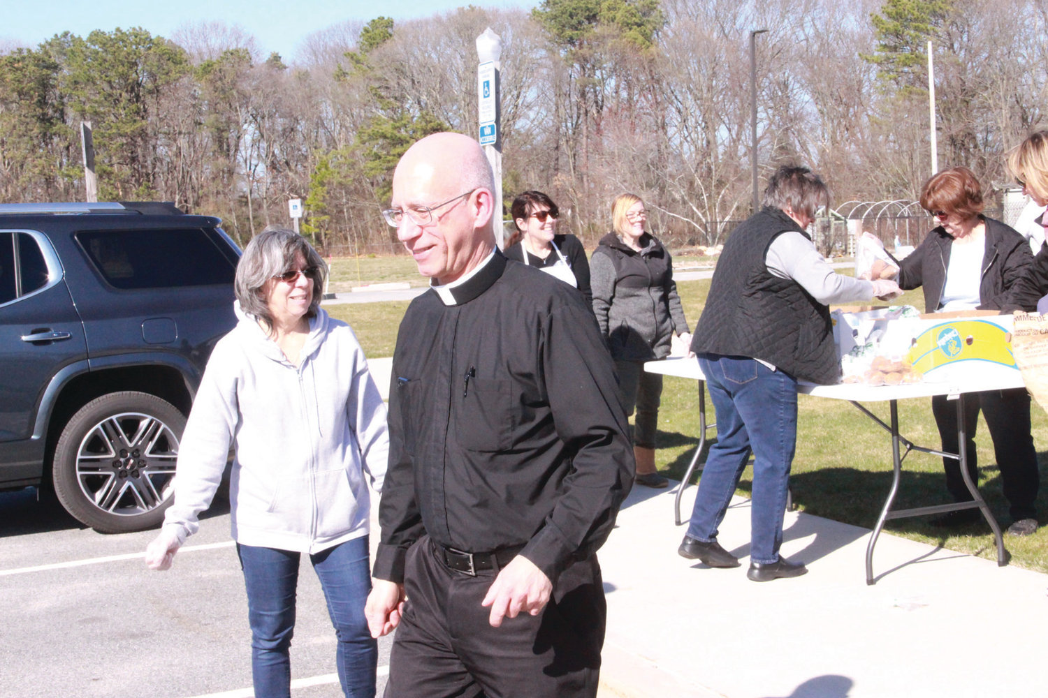 JOINING THE FLOCK: Saint Rose and Clement new pastor, Father Andrew  Messina, takes a break from his paperwork to greet his flock outside his office.