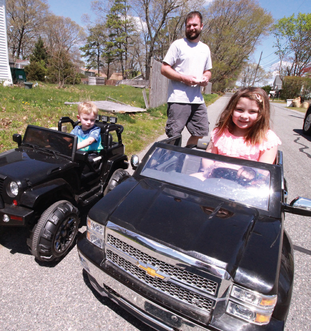 Brayden and Isabella Hartman under the watchful eye of their father, Jeremy line up on Shand Avenue for some driving or could it be racing, on Tuesday.