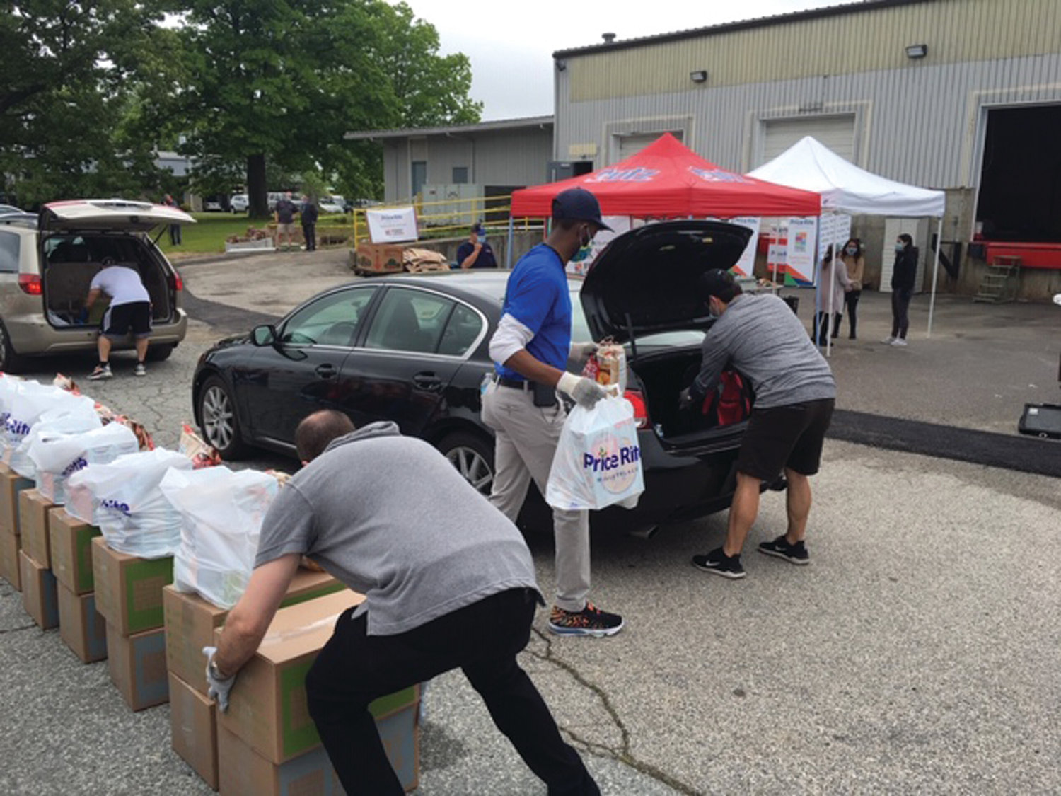 PACKING IT IN: Volunteers help load boxes and bags of food and other supplies into the vehicles of those who had obtained vouchers on line.