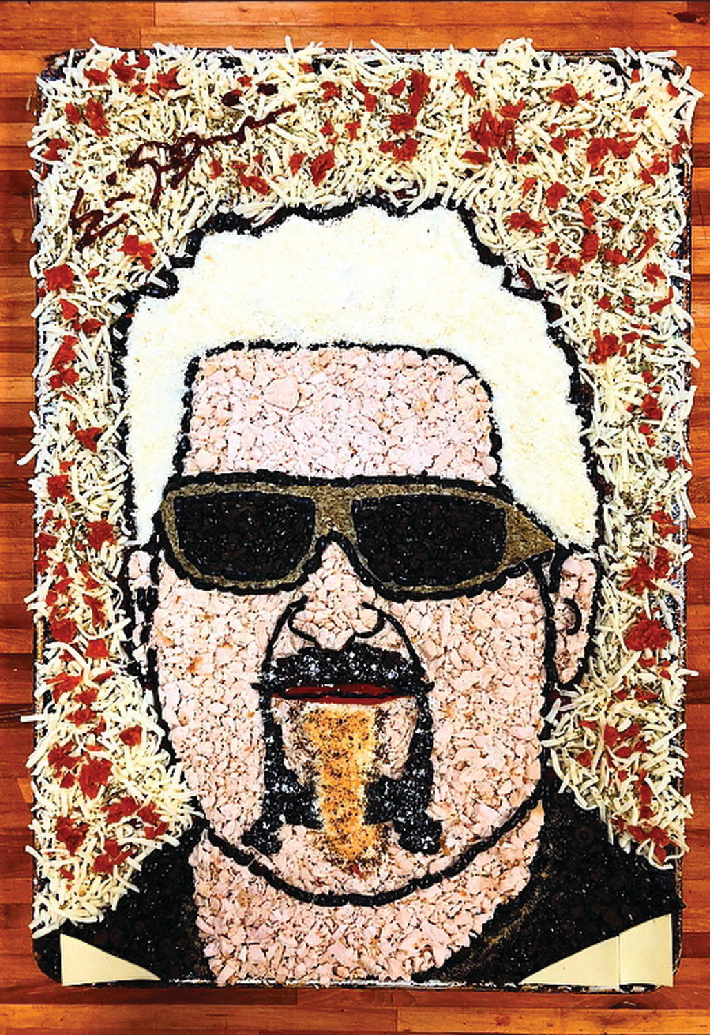 IN FLAVORTOWN: A portrait of Guy Fieri is one of Eric Palmieri's recent works of pizza art. He creates portrait pizzas for children, adults and even pets.
