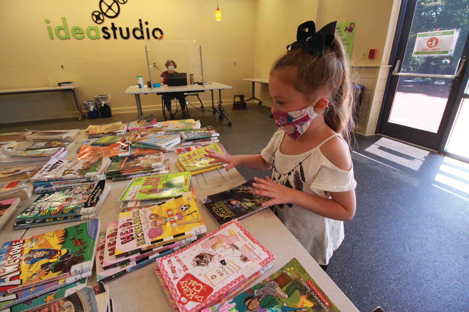 LOTS TO PICK FROM:  Six-year-old Mia Denoncour, a student at Sherman School, gets to pick out a book Monday.