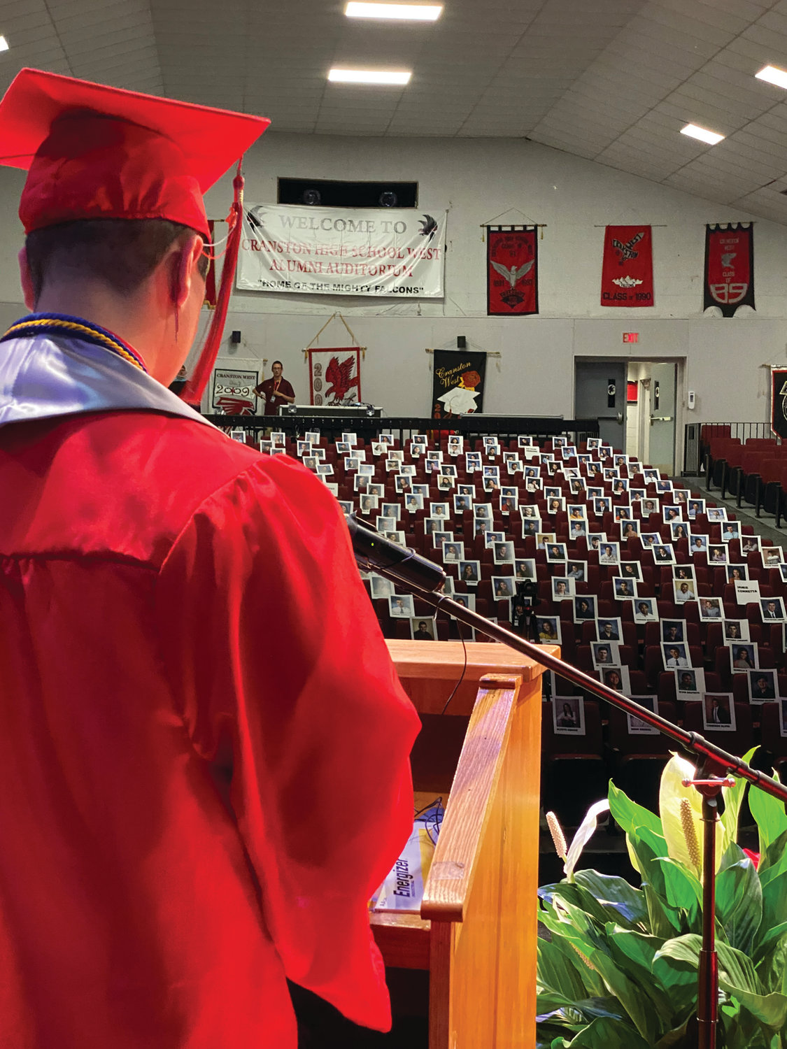 'YOU ARE ALL HERE WITH ME': Daniel Marella, salutatorian and president of Cranston High School West's class of 2020, delivers his remarks before images of his classmates in the school's Alumni Auditorium in early June. Marella, who spoke as part of a virtual graduation ceremony that was compiled in a video presentation that debuted over the weekend, at one point walked through the chairs to speak about several of his peers and their contributions to the school community.