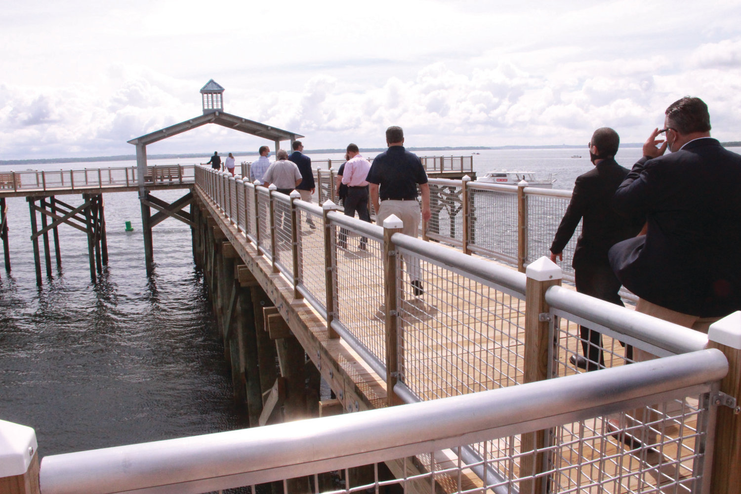 FIRST STEPS: The public walks on the Larry Mouradjian Rocky Point Fishing Pier for the first time after the ceremony Wednesday.