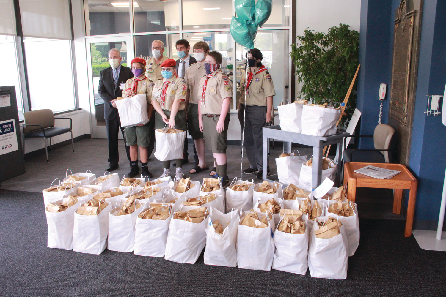 LINED UP  WITH S'MORES: Scouts from left to right, Rachel Levesque, Caitlyn Cunna, William Duckworth, (back) Mathew Duckworth, and (far-right) William Shealy, stand with Bob Haffey Kent Hospital President and Chief Operating Officer (far left), Tim McCandless Scout Executive and CEO of Narraganset Council Boy Scouts of America (left) and Yoni Sunshine development director for the Narraganset Council Boy Scouts of America (middle) in front of the 300 gift packages.