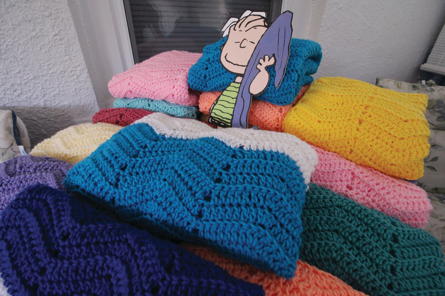 THERE TO COMFORT: This is just a sampling of the blankets Helen Smith has made for Project Linus. She averages 2½ blankets a week and has made more than 1,500 since 2007 to be distributed to hospitalized children and to be given out by first responders.