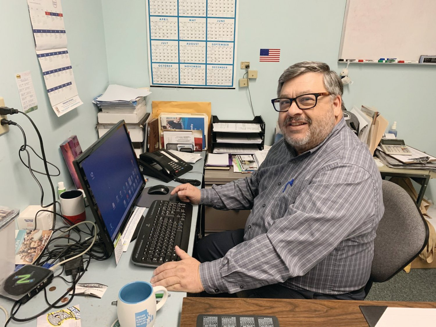 Bob Giberti, seen here at his familiar desk, is an expert in promotional products and marketing.  As the head of RhodyPrints, he will guide you through whatever products you need and can budget for to give your business more exposure or to make your event unforgettable.