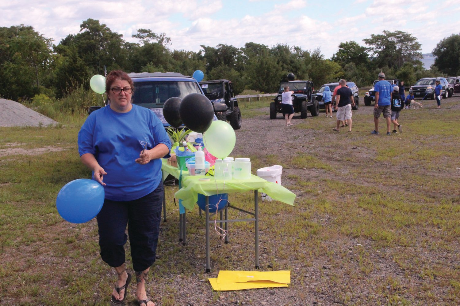 PUTTING ON A BRIGHT FACE: Balloons and messages written on car windows lent color to a somber occasion. Michelle Ciociola, pictured was the primary organizer of the event.