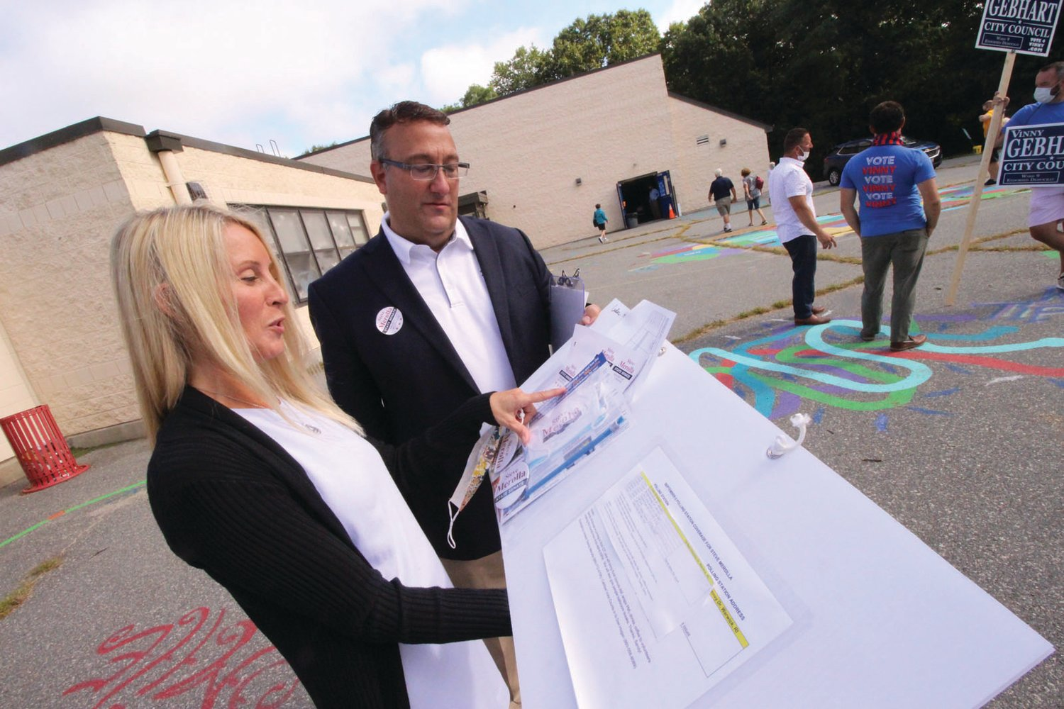 THE GAME PLAN: Michelle Merolla made double use of the sign she held in support of her husband, Steve Merolla. She had made pockets for a listing of polling locations as well as information if voters requested it. She and Steve are pictured outside Cedar Hill School.