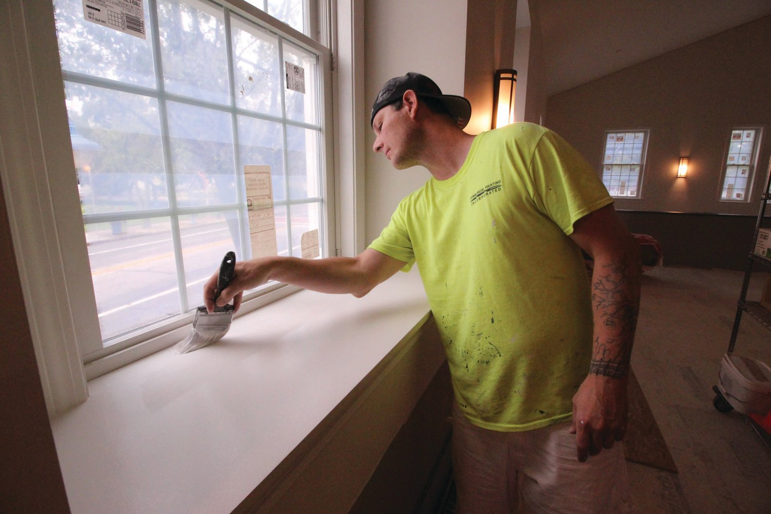 WITHOUT A BLEMISH:  Ray Hoffman of Commercial Painting in Pawtucket puts the finish coat on windowsills in the sanctuary. With baseboard heating having been installed and wall sconces installed, next steps include the chair railings and the flooring. (Warwick Beacon photos)