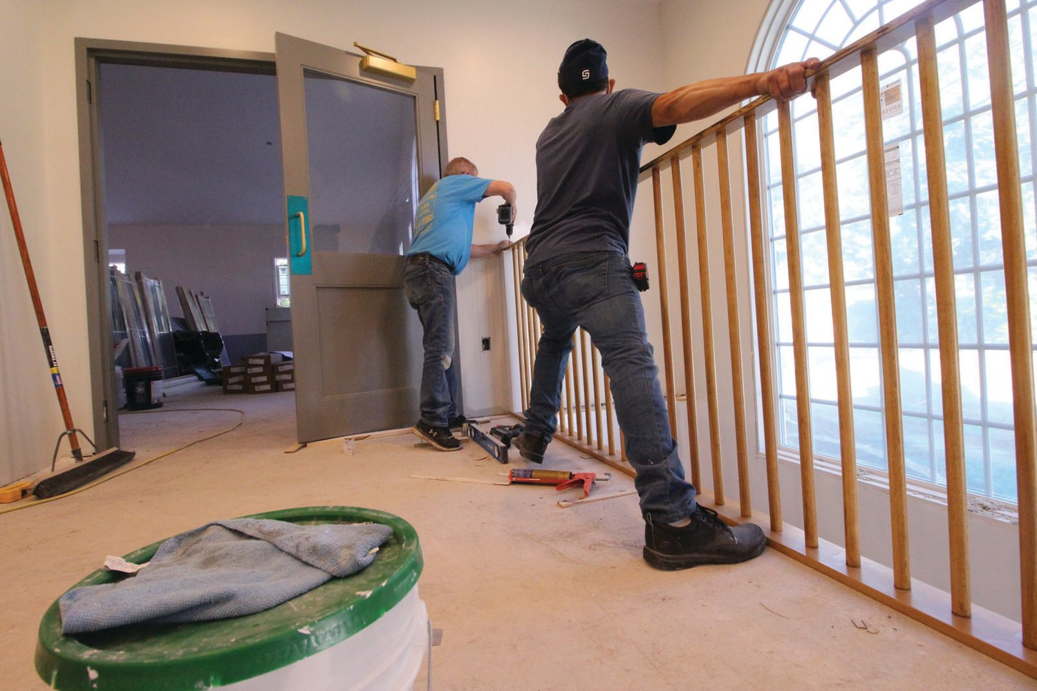 MADE TO FIT: Fred Moniz and Juan Gonzales of TNC Woodworking Inc., Pawtucket fit the banister and railing in the entrance to the church.