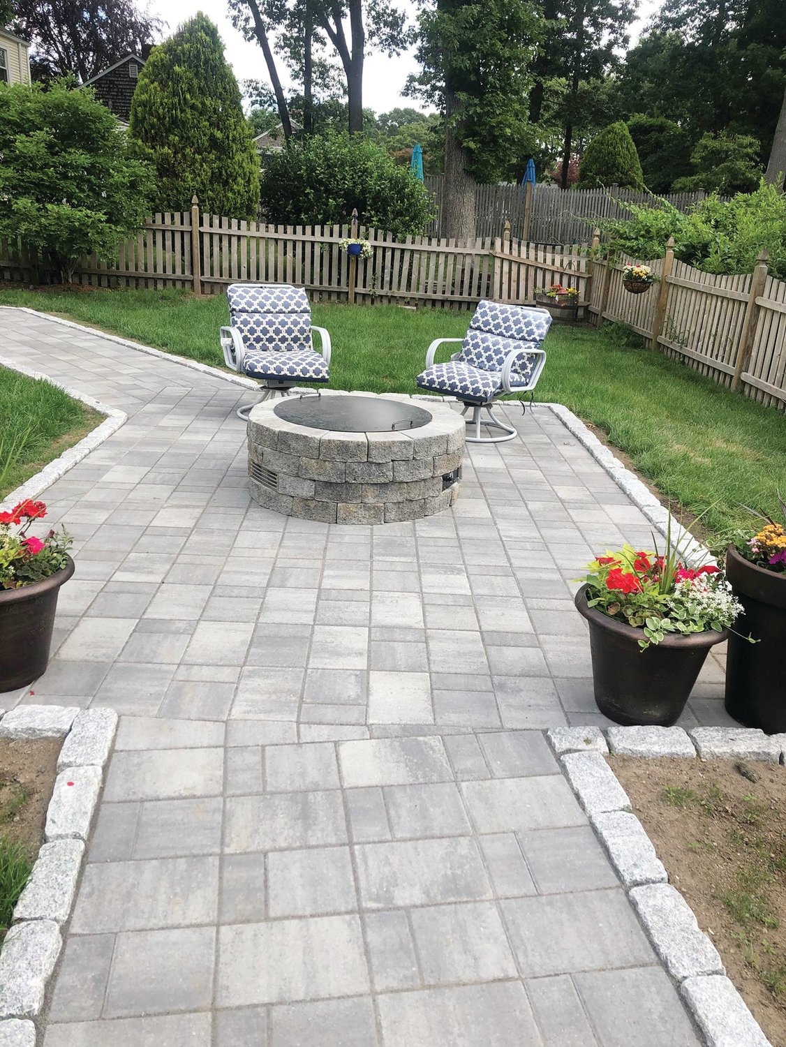 Spending more time at home during the pandemic inspires homeowners to renovate their yards with features such as this patio with fire pit installed by Yard Service Landscape Experts.