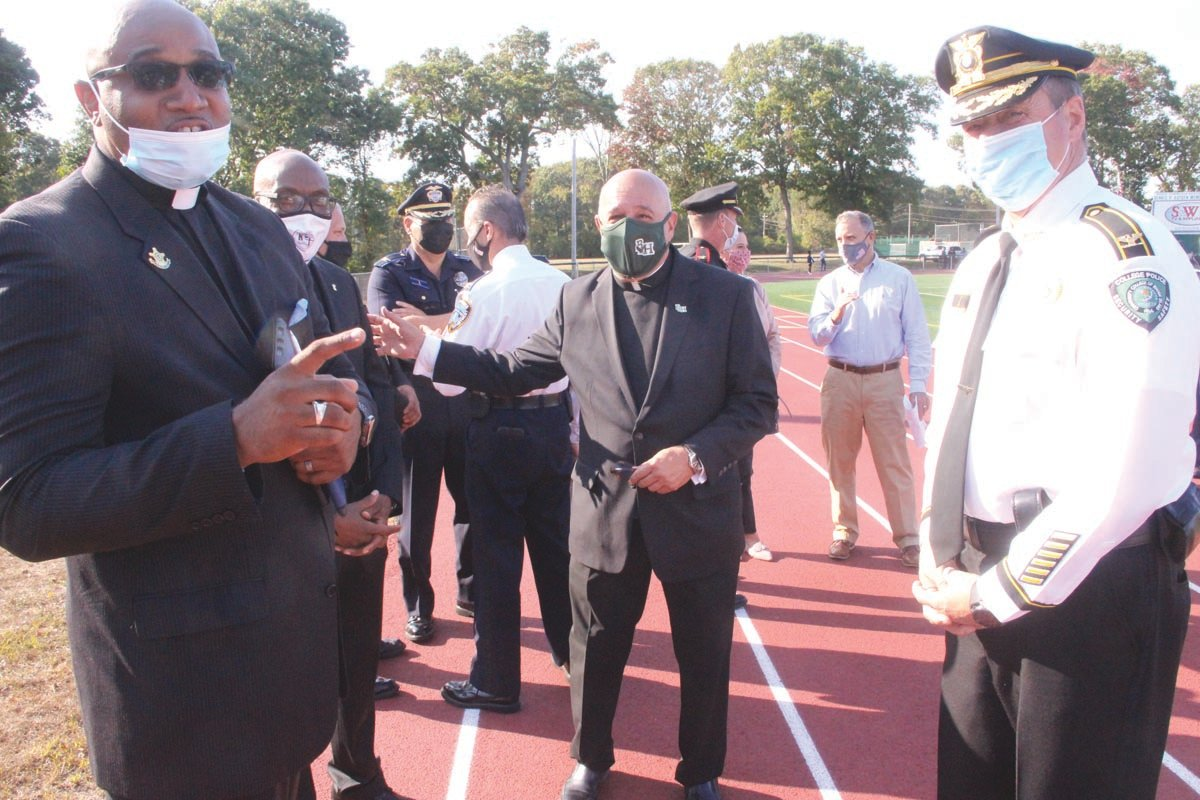 A HENDRICKEN GREETING: Fr. Robert Marciano, president of Hendricken High School, greets members of the faith and law enforcement communities to Saturday's event held on the football field.