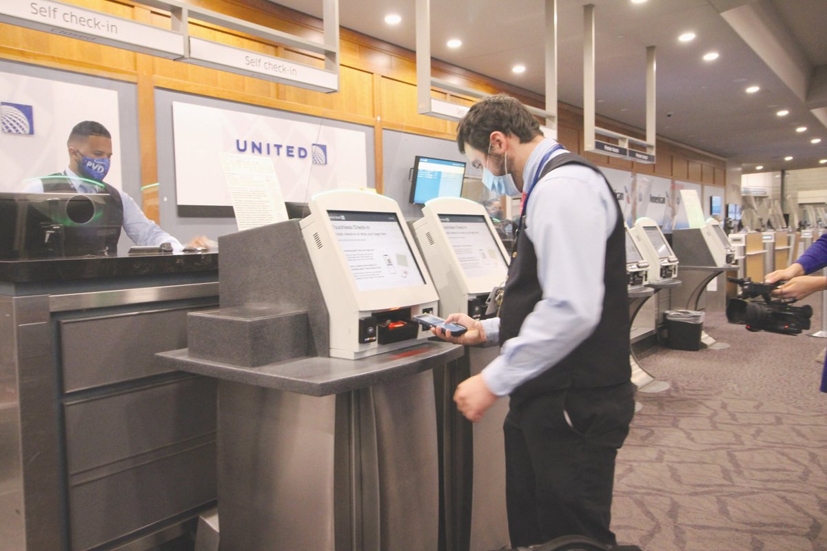DISTANCE CHECK IN: Using his cell phone, a United employee demonstrates how he can check in for a flight as well as receive a luggage ticket.