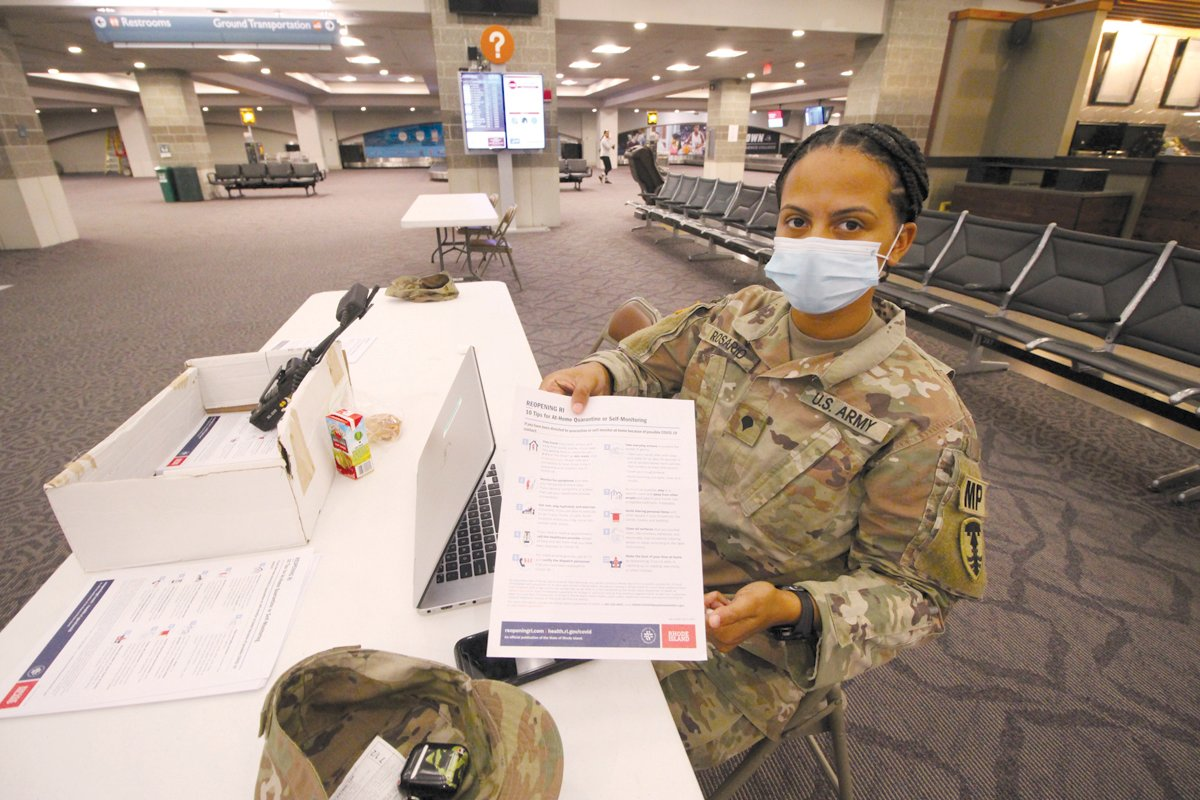 GETTING A HOLD ON COVID: Rhode Island National Guard Spc. Chantel Rosario greets arriving passengers at Green with an information sheet on reopening Rhode Island. The sheet lists 10 tips for those who have been directed to self-quarantine.