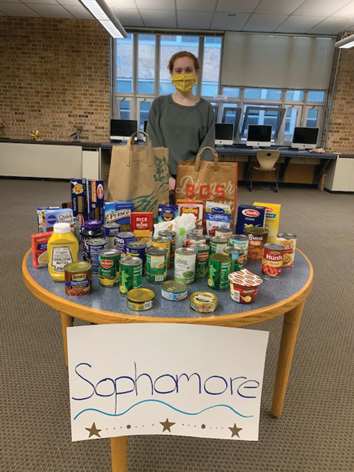 LENDING A HAND: Vice President of SADD Melanie Vessella helps to collect cans at the sophomore class table.