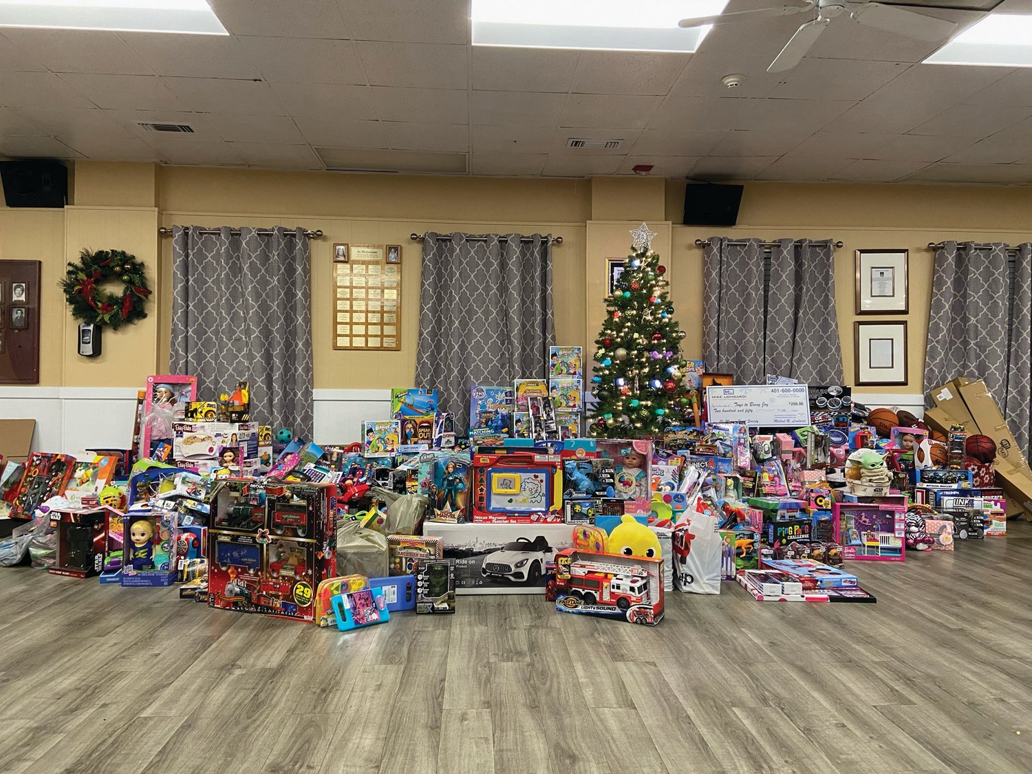 BRINGING JOY: Donated toys surround the Christmas tree at the St. Mary's Feast Society building in Knightsville. The toys will be distributed to families in need during a community giveaway this weekend.