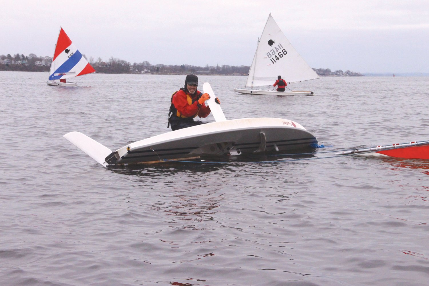 WORKING TO GET IT UPRIGHT: Rich Glucksman applies weight to the centerboard after taking a dunking while maneuvering for the first race. Fellow sailors remained close by to check on his condition.