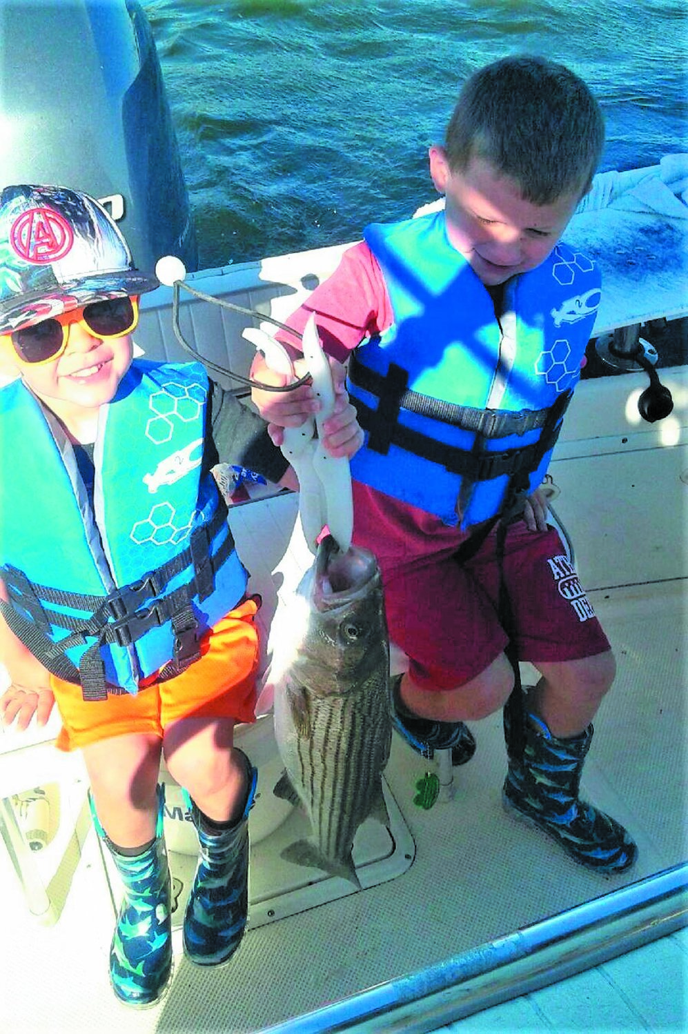 STRIPER AMENDMENT: Eli (3) and Andre (5) Swain of Richmond with their first striped bass a year and a half ago when fishing with grandfather Mike Swain. Fish managers are asking for angler input … speak up, we need to keep our youth fishing.