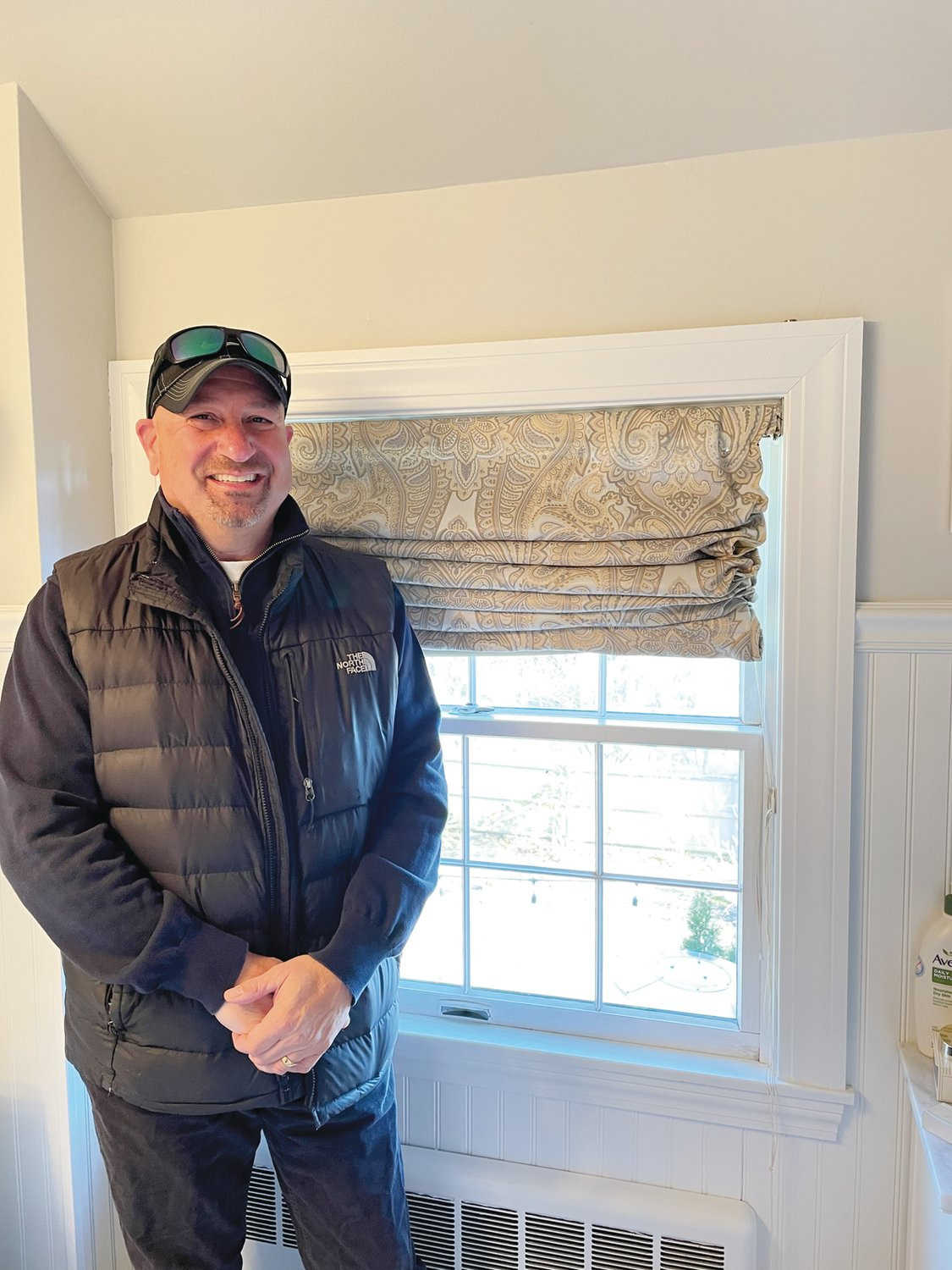 Meet Harris Alkins, seen here ready to measure the bathroom window of a Warwick resident who has decided to ditch the room's roman shades in favor of some long-lasting, traditional shutters.