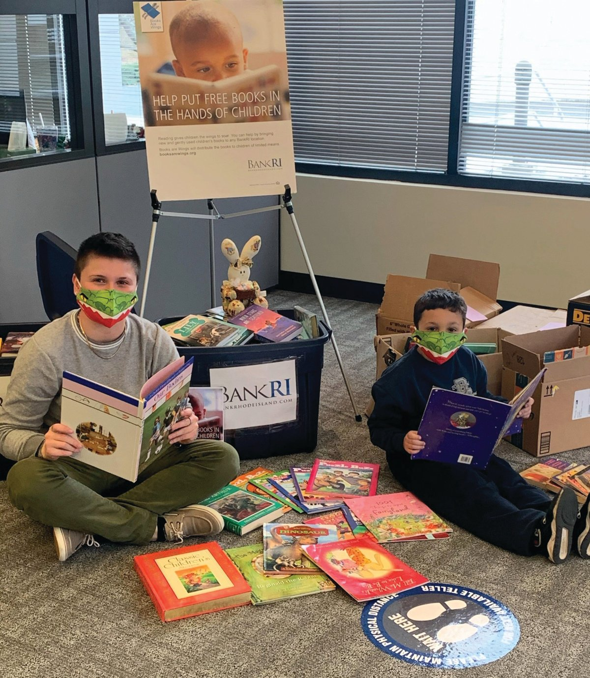 It's Always a Good Time to Read: Steven Fennessy, 7, takes a moment to give a final read to one of the 11 books he donated at BankRI's Atwood Avenue branch in support of this year's Children's Book Drive. He's joined by Hannah Page, a BankRI teller.