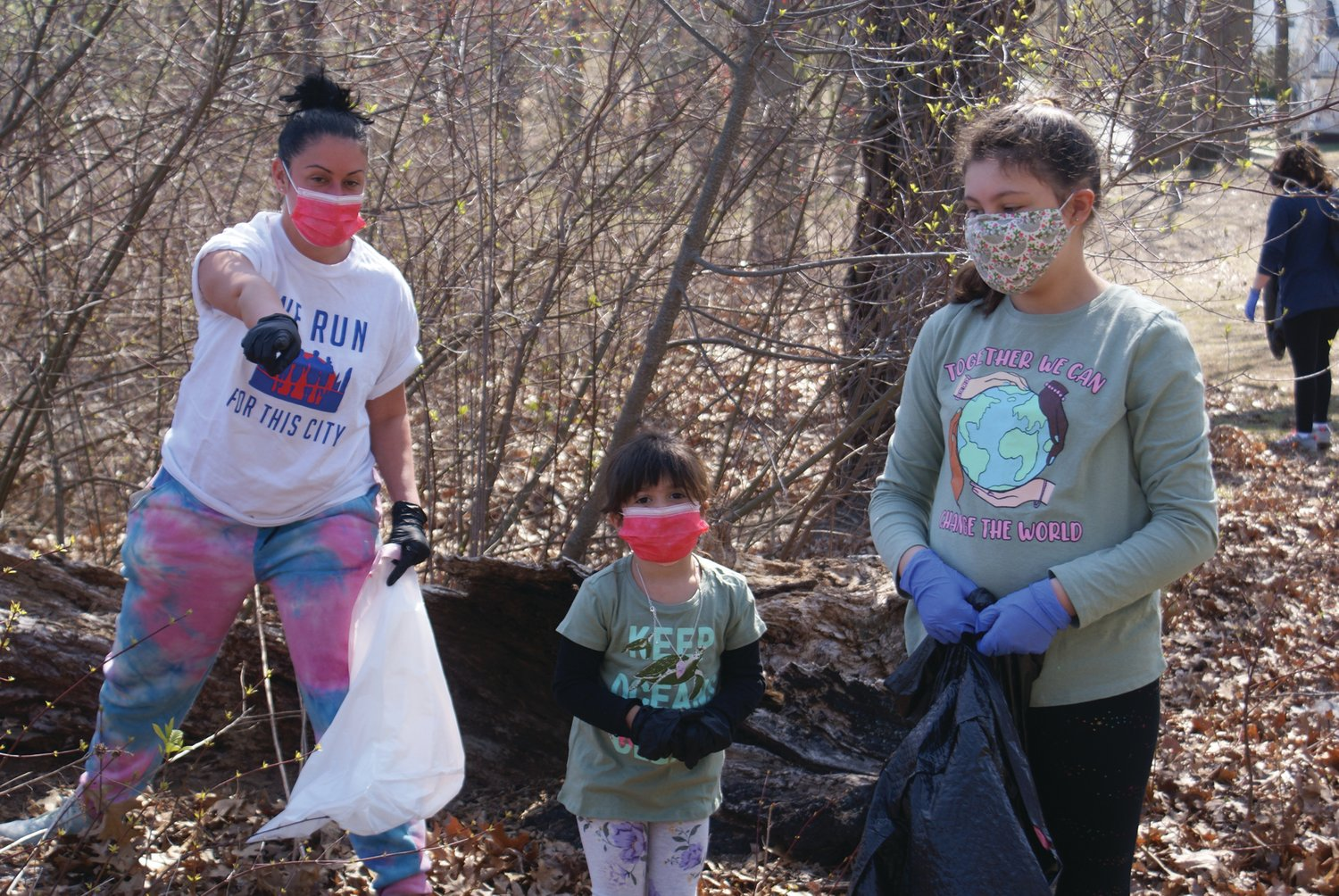 CLEANING UP: Citywide Councilwoman Nicole Renzulli points to trash found in Meschanticut Park as her daughter, 4-year-old Francesca Martins, and Sophia Paplauskas look on.